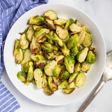 Air fried Brussels Sprouts in white bowl.