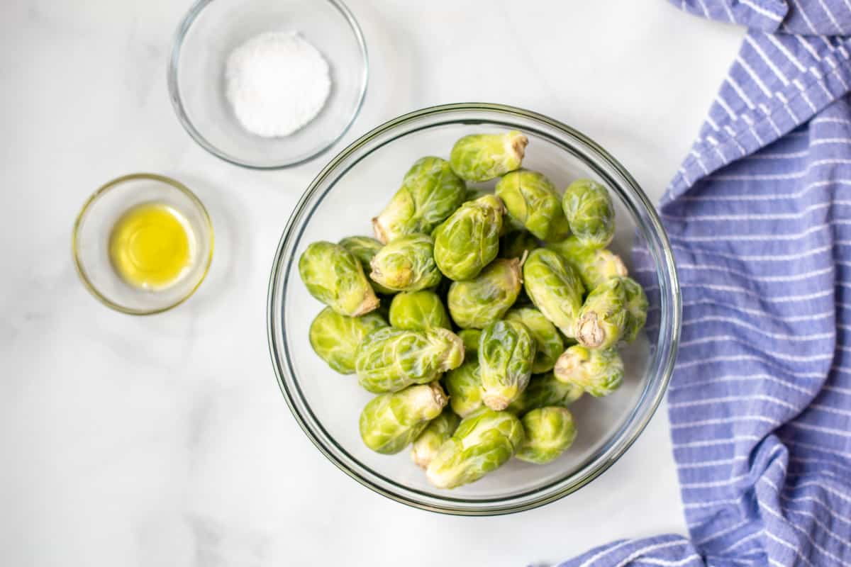 Bowl of Brussels Sprouts next to olive oil and salt.