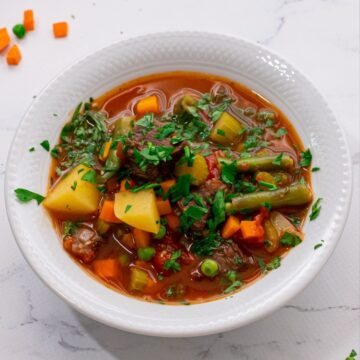 Bowl of Vegetable Beef Soup topped with parsley.